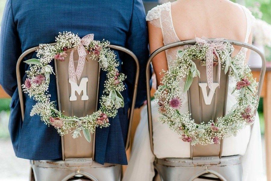 Coronas de flores con gypsophila como decoración para las sillas de los novios …
