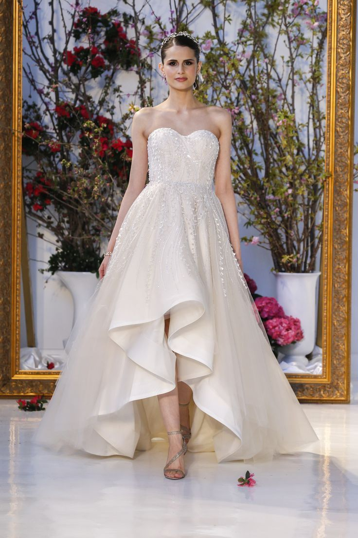This strapless high-low A-line gown features an empire ...