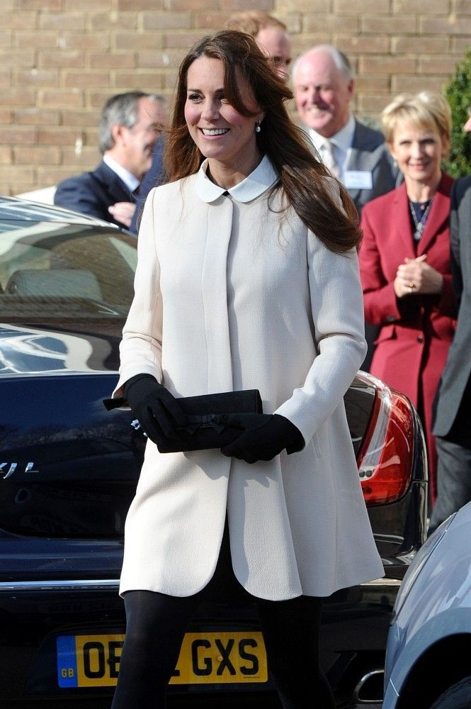 Kate Middleton wore a mod-inspired white coat to top off her classic retro look while visiting a charity.