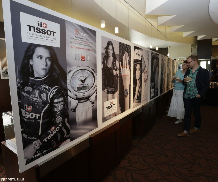 Celebrating 10 years of Danica Patrick.  Attendees take a walk down memory lane with Danica's Tissot ads through the years on display.  Indianapolis, 7/25/15.  HHP/Harold Hinson