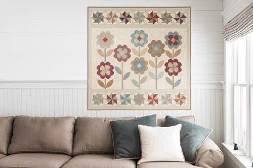 """Poppies Garden Kit Lend a charming, homey look to your decor with the pieced flowers and pinwheels in this quilt. Kit has directions by Terri Degenkolb of Whimsicals, and fabrics for the top and binding from L'Atelier Perdu's Pauline line for Windham Fabrics. Throw 60"""" x60""""."""