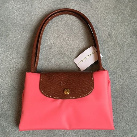 cb24ac003854 100% Authentic Longchamp bag in rich peach color! Perfect for spring! This  brand new with tags rich peach colored bag is a medium size with long  handles!