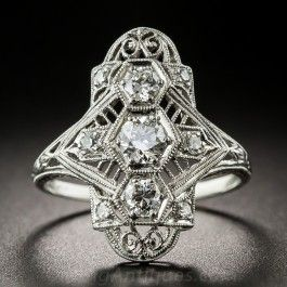 Seven-eighths inch long and lovely, a consummate Art Deco diamond 'right-hand ring', or dinner ring, crafted in platinum and exquisitely detailed with die-struck, hand finished filigree work and accentuated with delicately applied milgraining throughout. Three bright-white European-cut diamonds sparkle from hexagonal settings and are each flanked with a twinkling single-cut diamond on each side. A classic Jazz Age jewel. Currently, size 6 1/2.