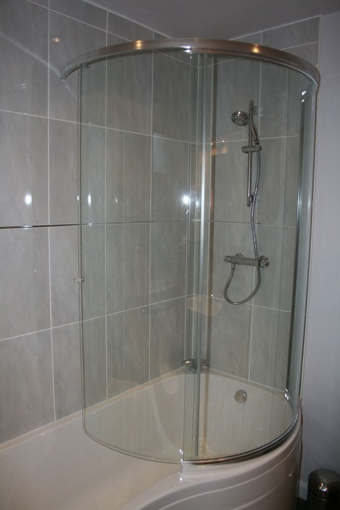 Cylindrical shower cubicle with glass panels in curved bathtub. Make ...