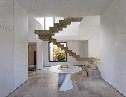 Een opvallende betonnen trap hangend in het c house vormgegeven