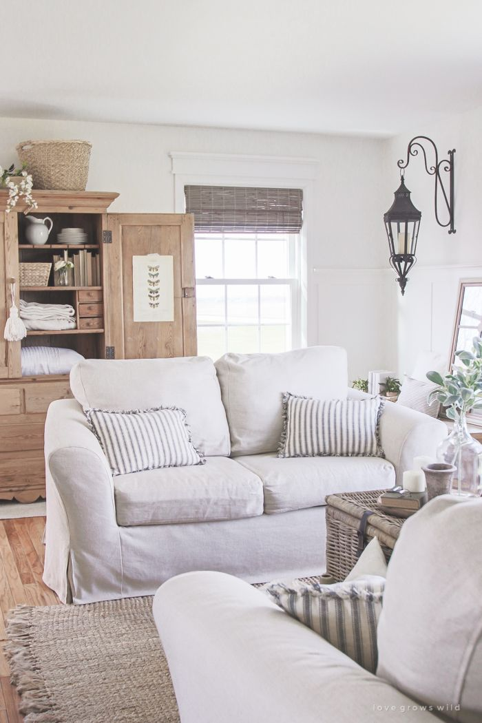 A Cozy Farmhouse Living Room With Beautiful Linen Slipcovered Sofas. See  How To Get This