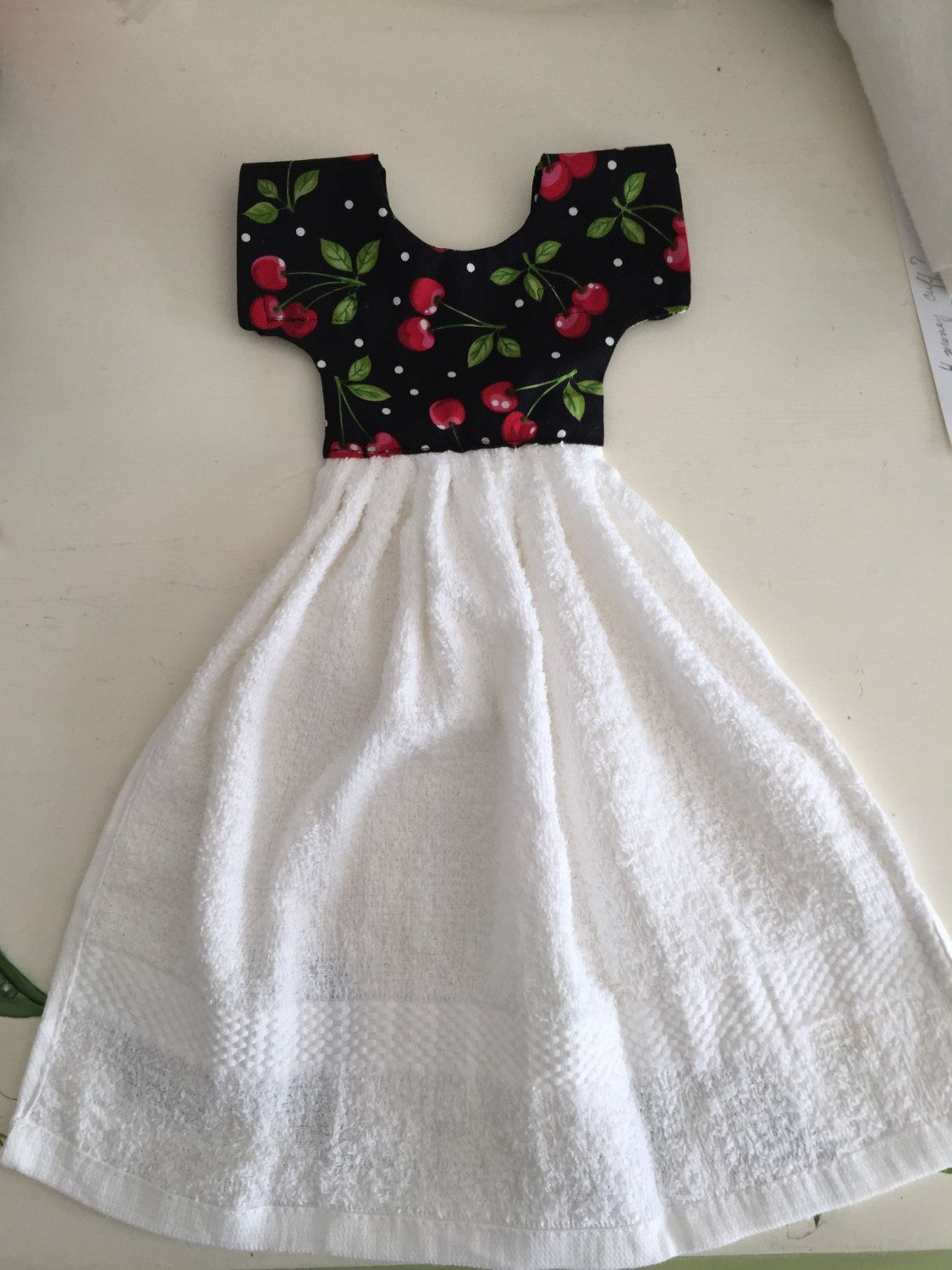Kitchen towel, looks like a dress which hangs from a handle of oven ...