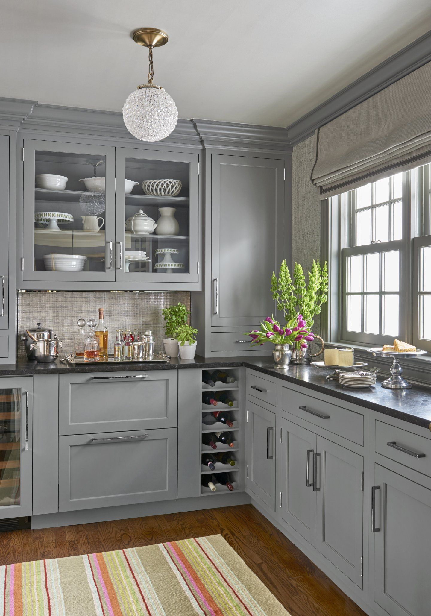A first class butlers pantry boasts leatherized black granite countertops silvery grasscloth wallpaper and a sparkling ceiling fixture