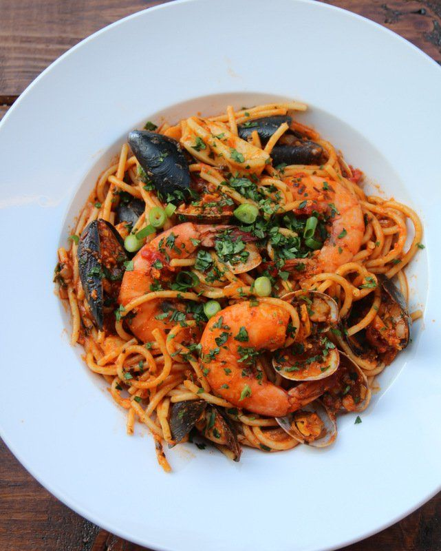 Latin style seafood spaghetti recipe, or tallarines con mariscos, made with a mix of seafood – fish, shrimp, mussels, scallops, clams, and calamari - cooked in a sauce of tomatoes, onion, garlic, cilantro, cumin, and achiote.    - Recipe & Photo; Laylita's recipes