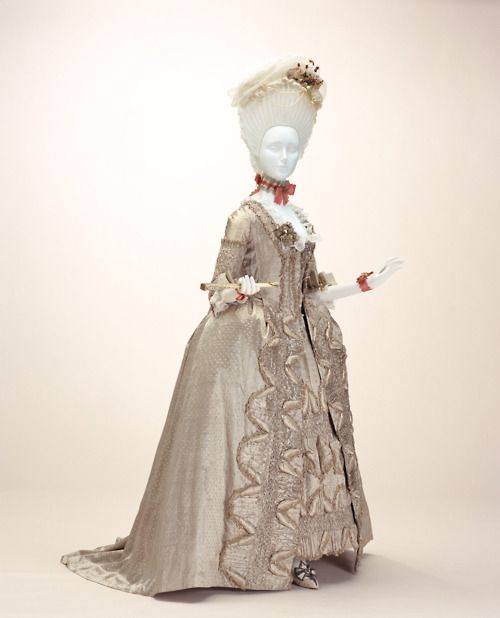 "Dress (""robe à la française"") c. 1775-France Material: Beige silk satin with thin stripe and dot pattern; ""compères"" front; matching petticoat; padded three-dimensional decoration; trimmed with fly fringe and chenille.A dress that demonstrates the magnificence achievable with hand work. The subdued impression given by the elegant monochrome all the more augments the tranquil refinement of numerous ornaments created by needle and thread, along with raised decorations that"