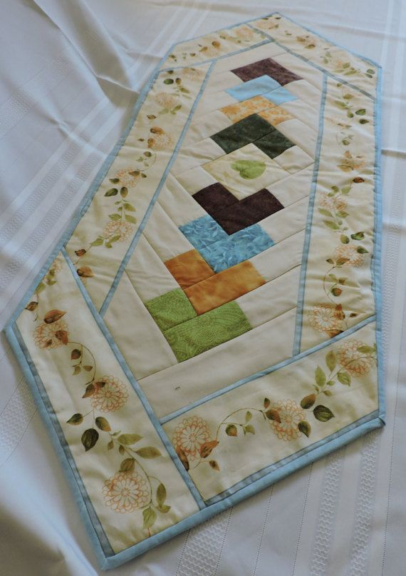 A quilted table runner thats perfect for spring. The border print of daisies on a cream background surrounds a center of overlapping squares in