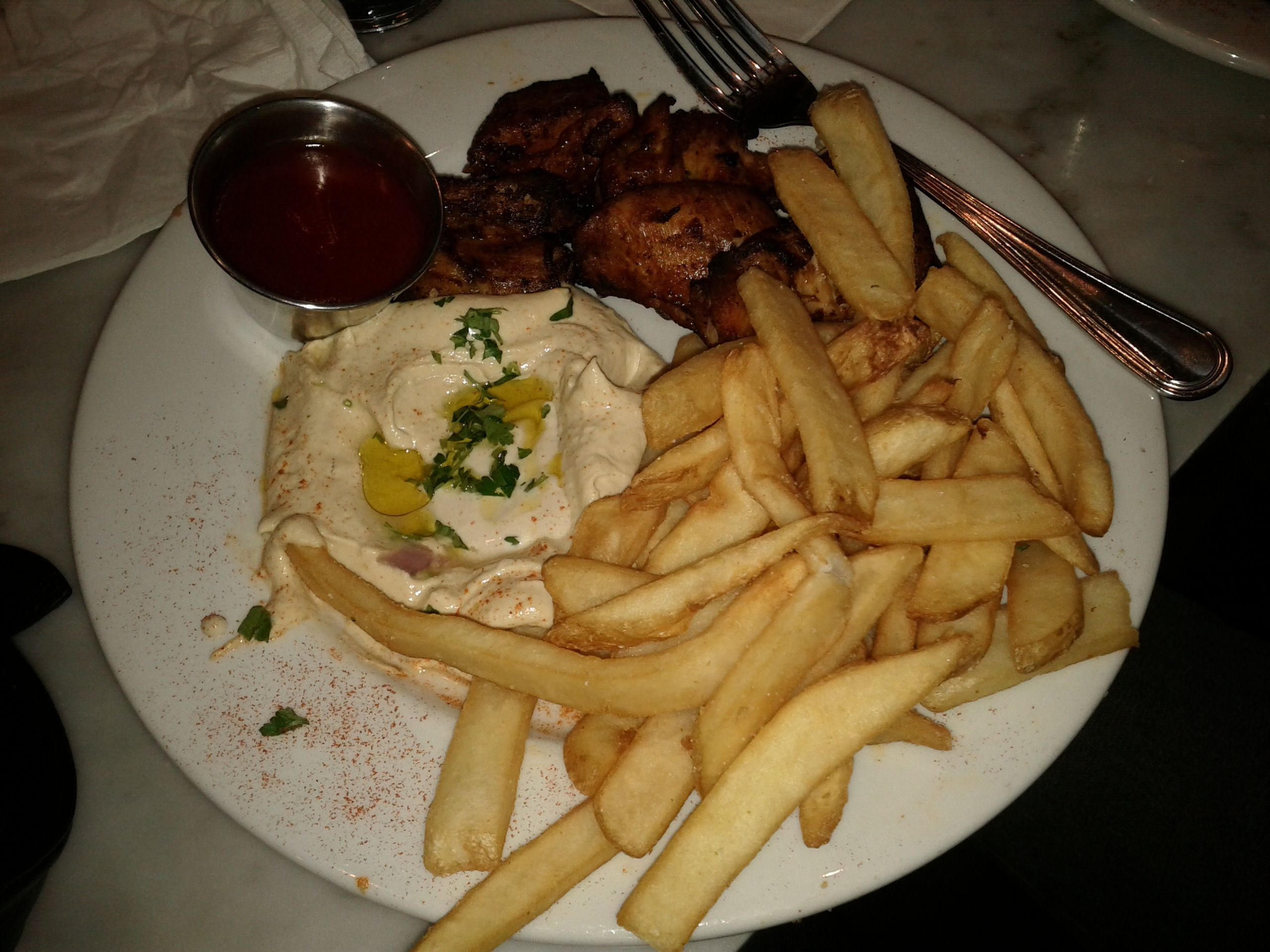 Chicken skewers with hummus and fries at orens hummus