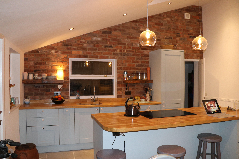 Kitchen with brick wall blue kitchen units wood worktop glass