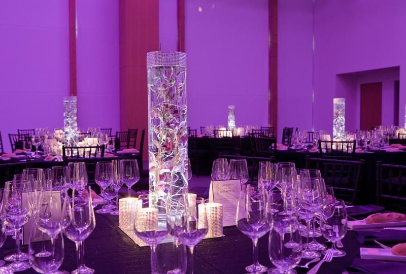 Single sleek centerpiece, with gorgeous purple wedding reception lighting.