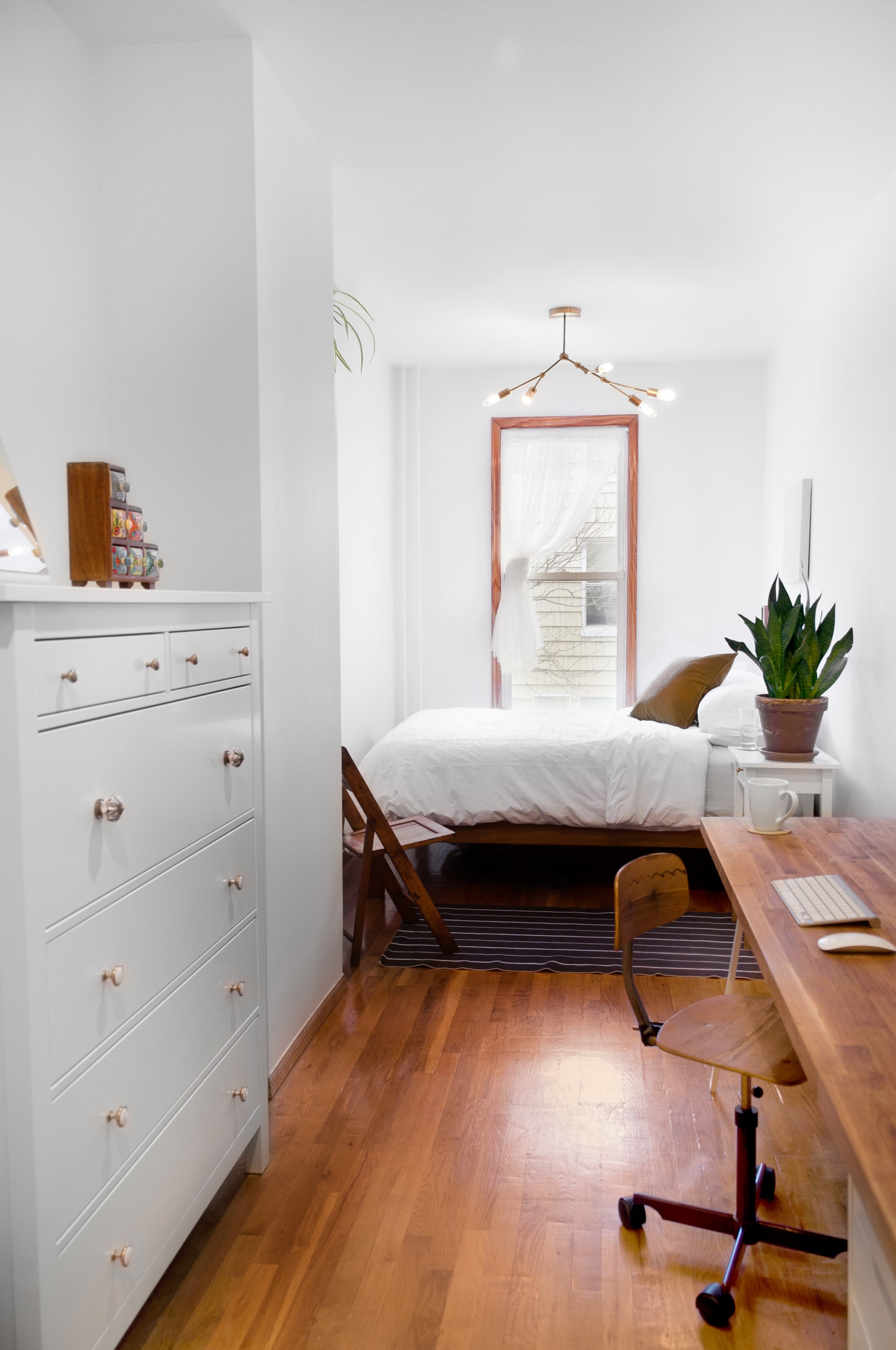 Small white apartment with bed, dresser and wooden desk. Keeping the color palette simple ensures that your small bedroom will remain restful and calming.