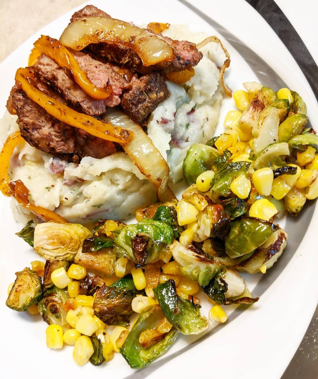 Tender steak on smashed red potatoes with a side of roasted brussel sprouts and corn #smashedbrusselsprouts
