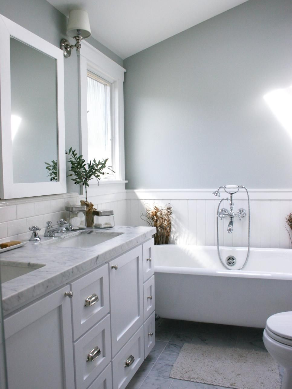 A white bathtub, backsplash tile, mirror and window frame contrast ...