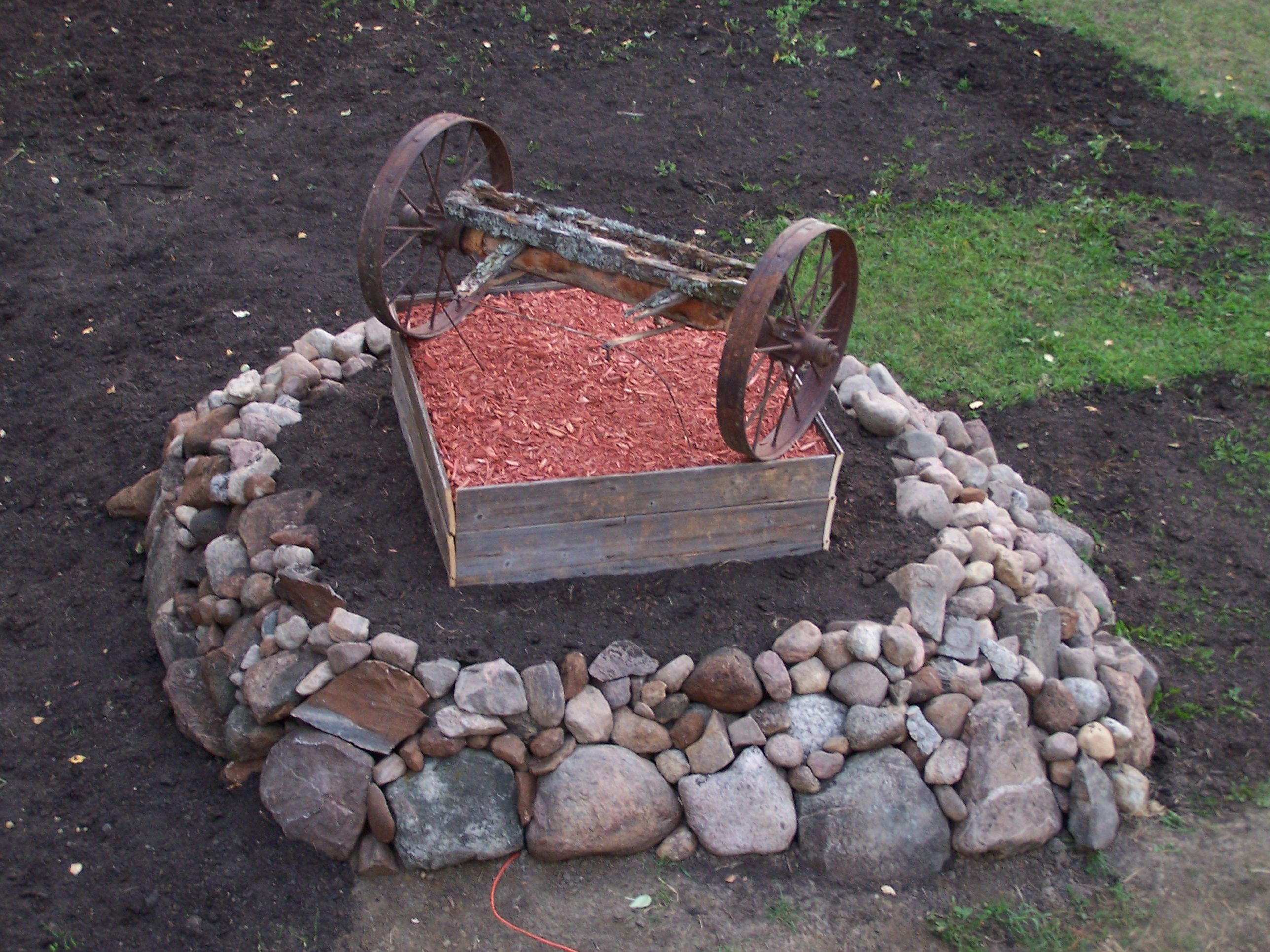garden ideas old steel wagon wheel axle and rock surrounding flower bed covering up septic tank lid