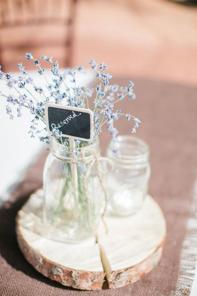 Sweet (and cheap) rustic centrepiece - lavender, twine, mason jars, a wood cut off & mini chalkboard signs. photo by This Girl Nicole