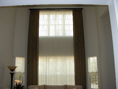 Two Story Tall Windows With Functional Sheers And Decorative Side
