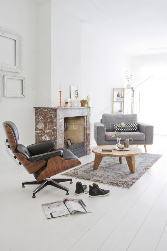 black eames lounge chair in a white light living room fire place