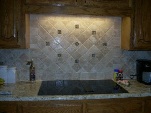 Travertine backsplash with oilrubbed bronze deco inserts JFE