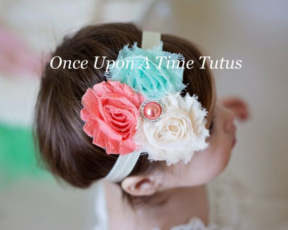 A coral, mint, and ivory shabby flower topped with a faux pearl rhinestone on a soft and stretchy ivory elastic band.    ** Perfect newborn,