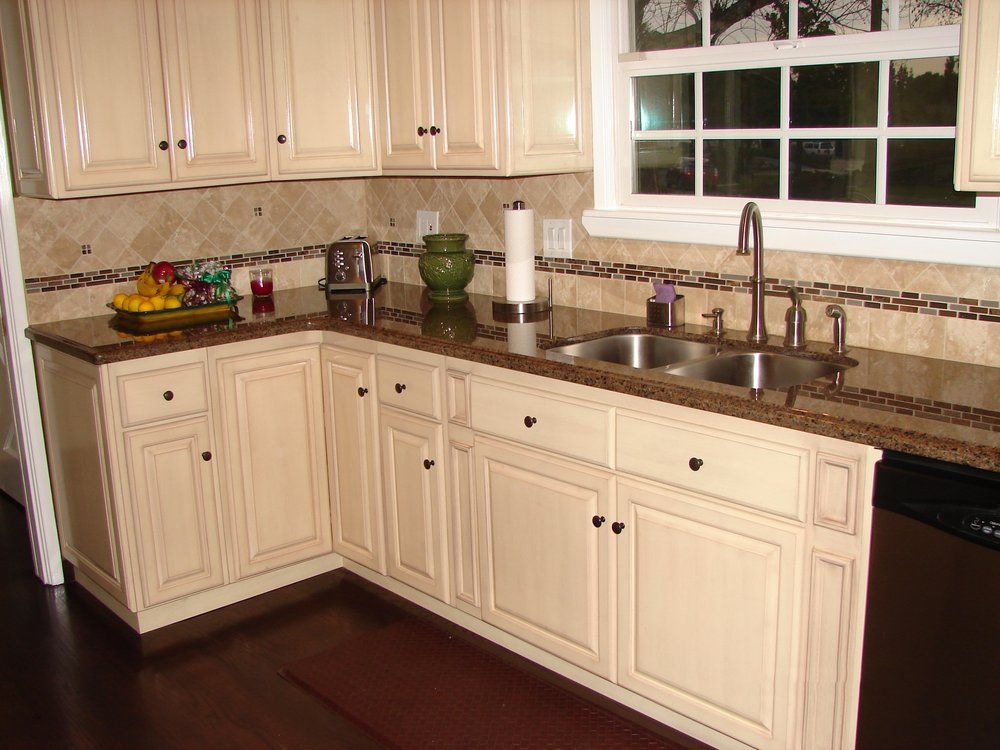 Antique white raised panel cabinets and tropical brown for Pictures of white kitchen cabinets with granite countertops