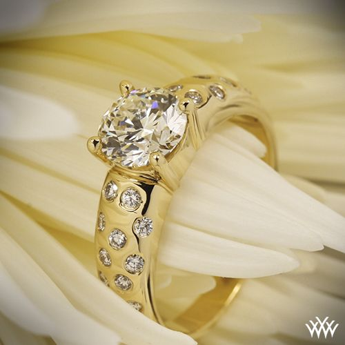 Custom Diamond Engagement Ring is set in 18k yellow gold and features a scattered diamond shank that sparkles with A CUT ABOVE® Hearts and Arrows Diamond Melee. The 4 prong head holds a gorgeous 1.218ct A CUT ABOVE® Diamond.
