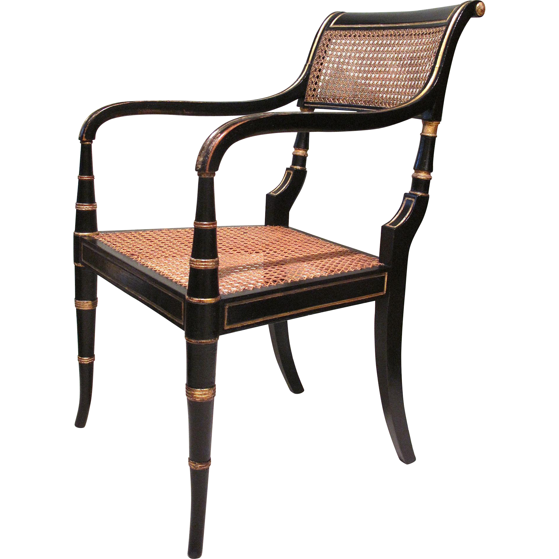 An elegant black japan painted and parcel gilt armchair, ca. 1810, with backswept rear legs and back. Retains most of its original gilding. Front legs