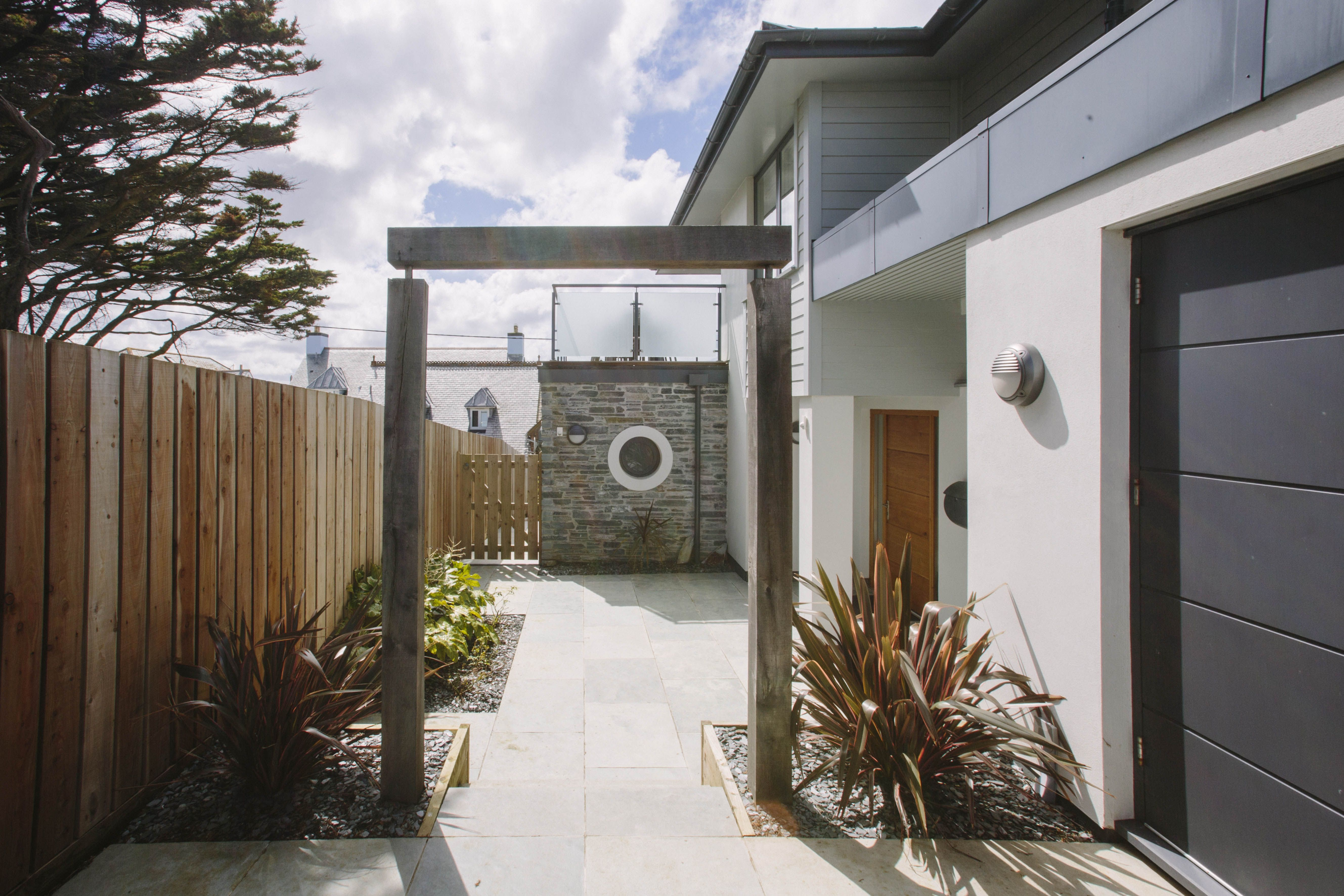 Rosemar is a striking three-storey house created from a beautiful combination of stone, glass and wood. Stylish wooden archways, porthole windows and carefully planted beds create a contemporary ambience.