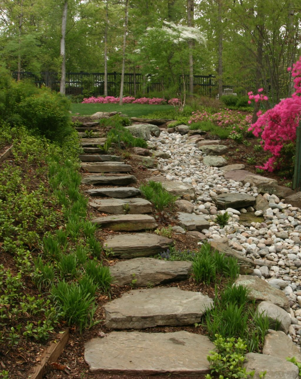 The natural stone steps of a stairway garden feature climb a small - Dry Creek Bed Effect On Slope With Stairs Via Merrifield Garden Center