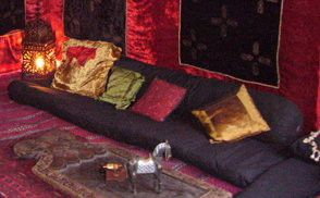 Black Floor Level Sofa With Back Bolster And Colourful Cushions