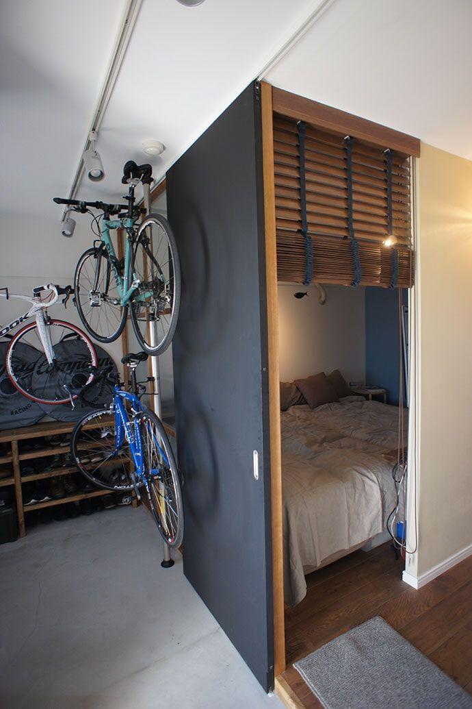 3台あるロードバイク置き場 所は 自分たちでメンテナンスもするために 玄関とつながる広い土間スペースとして確保した その隣にはモールガラスを間仕切りに利用した寝室 が隣接し土間に差し込む光を取り込める 限られた空間のため 寝室は完全個室にはせず テレビを