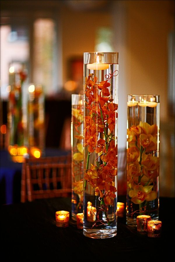 Orange orchids submerged in water with floating candle