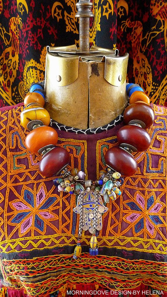 by Helena Nelson Reed | Central pendant combines a contemporary enamel Hamsa/Hand of Fatima from Morocco,combined with an assortment antique, vintage and a sprinkling of contemporary glass trade beads. The main necklace has been made from large cherry and golden amber resin beads (contemporary mock - amber made in the traditional fashion). Vintage African coins, serve as spacers. The blue glass beads near the neck are old glass traded into Africa in the late 1800s to early 1900s | Sold