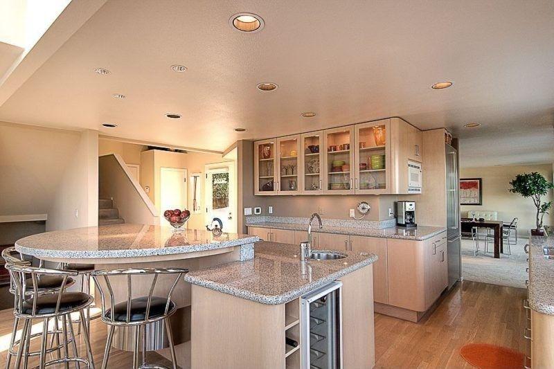 Diese aus weißen Küche verfügt über eine Reihe von Schränken und - offene küche mit insel