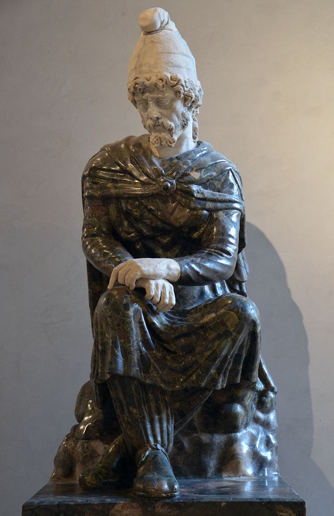 """The head covered with a Phrygian cap dates from the 2nd century AD and is reminiscent of the famous """"Prisoners"""" in the Palazzo Farnese; the latter, who probably represent defeated Dacians, are thought to date from the reign of Trajan and may well come from the Forum of Trajan itself (AD 98–117). The body probably dates from the 1st century AD and represents a defeated Oriental. The reassembled statue stood at the centre of the """"Room of the Conquered Barbarian King"""" in the villa built in…"""
