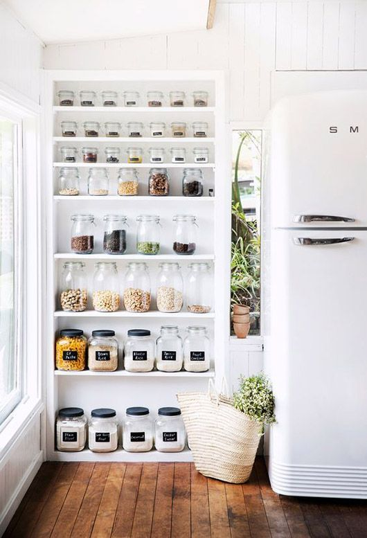 glass jars on shelves and white smeg fridge in modern kitchen. / sfgirlbybay