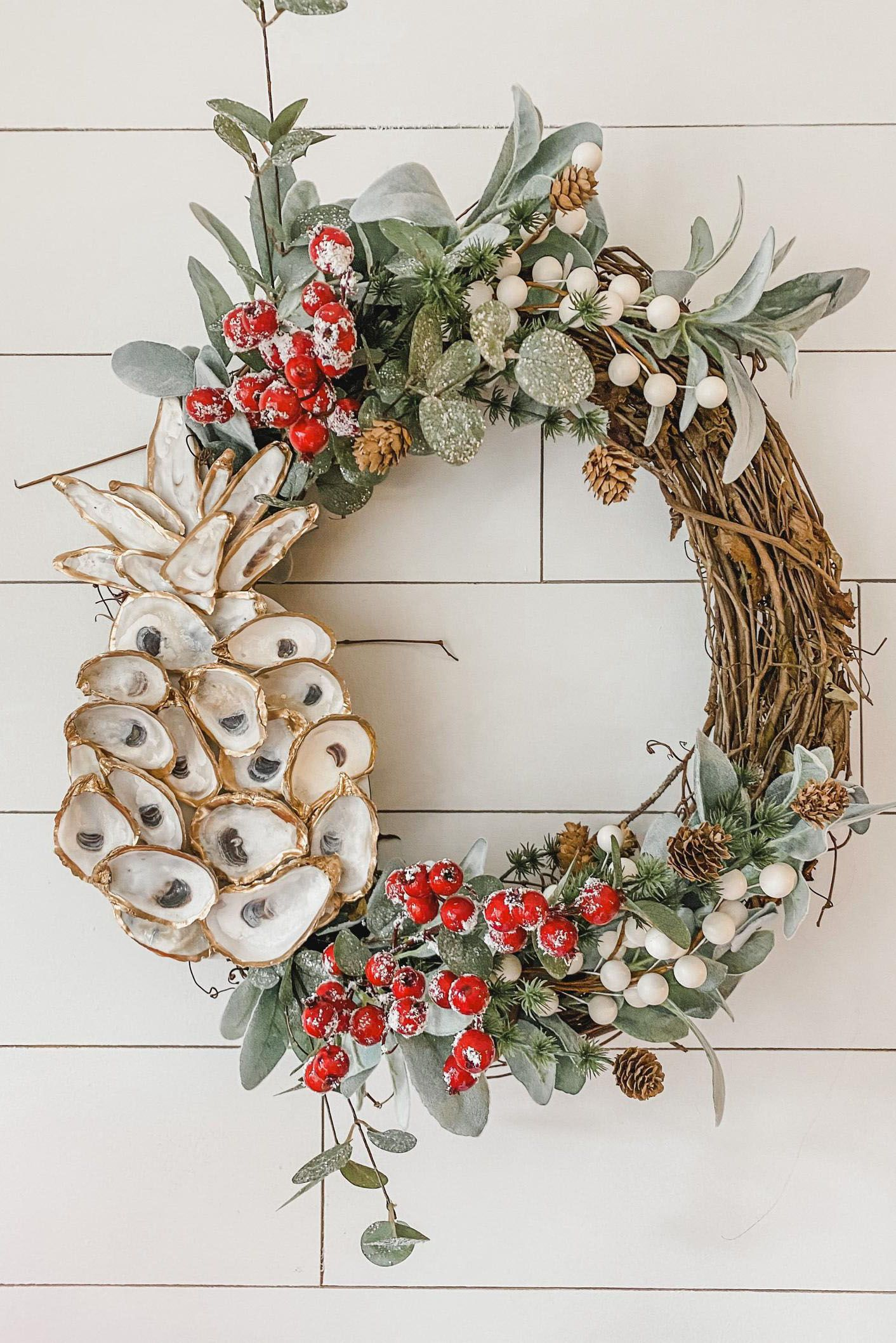 Beautiful tropical holiday wreath with an oyster shell pineapple. This grapevine wreath has a mix of Christmas pine and pine cones, lambs ear greenery, sparkle eucalyptus, red snowy berries, and white berry floral accents.