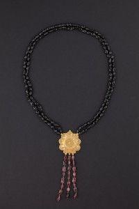 Collana  Collana realizzata da due fili di tormalina nera che reggono un pendente centrale in oro, di antica manifattura indones