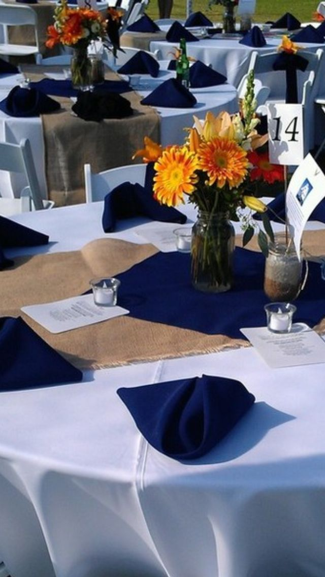 Orange flowers and navy nautical centerpiece with ships on table.