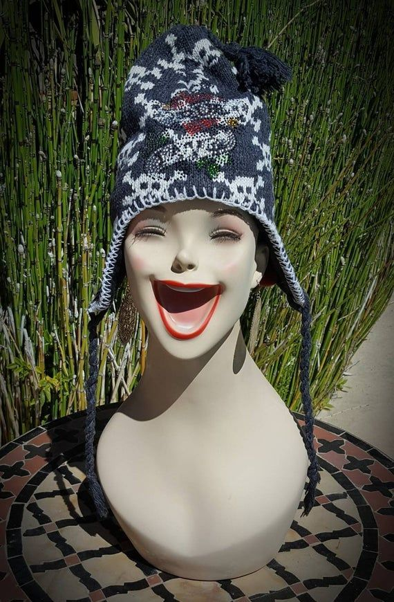 Lots of Skulls and Bones on this beanie. Earflap Hat in  SuperSoft acrylic/cotton blend. Braided tassels hang from both earflaps, Knit Pattern is Skulls and Bones design, Grey and White,  embellished with Tattoo Looking Heart