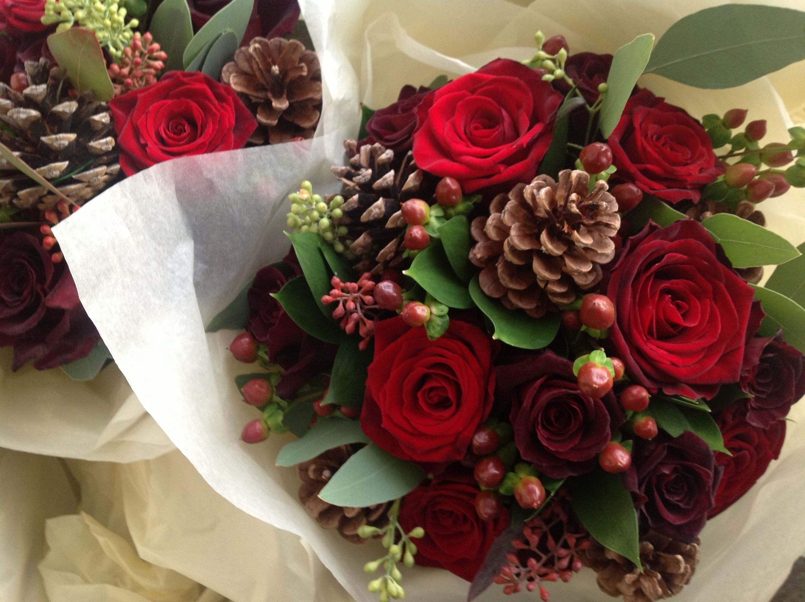 red rose hypericum and dark green foliage no pine cones use ivory roses instead