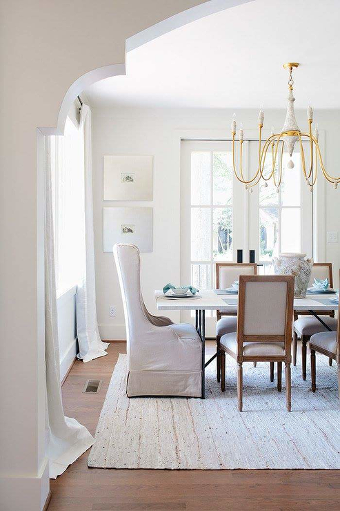 Beautiful Transitional Dining Room Is Fitted With A Gold Candle Chandelier  Hung Over An Iron And
