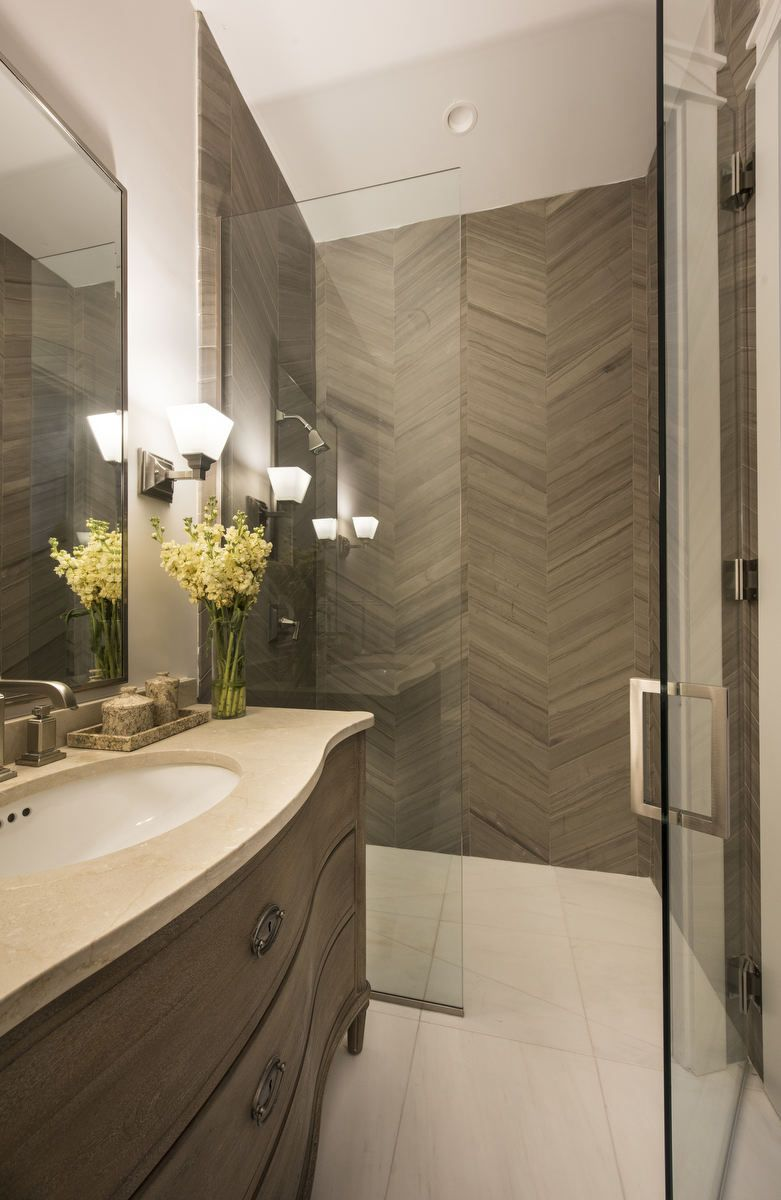 In a small bathroom we chose to add a focal point with a rustic this glass enclosed shower features a stylish taupe tile herringbone pattern and large neutral floor tiles a wooden dresser like vanity with a neutral dailygadgetfo Images
