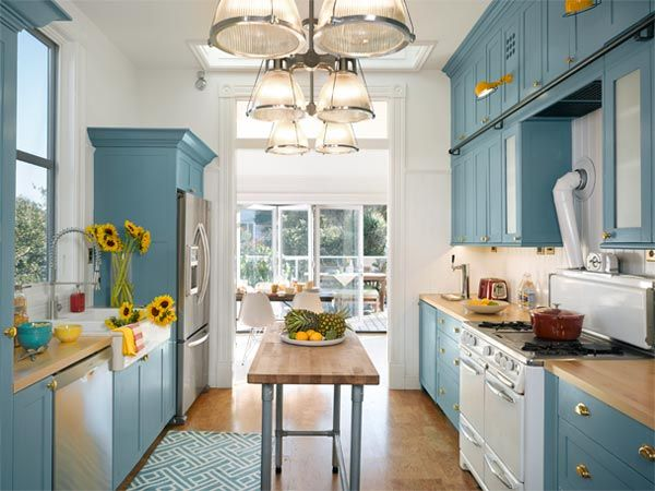 Opened up to the sun this galley kitchen is blue and white and bright all over with a vintage wedgewood stove as its centerpiece