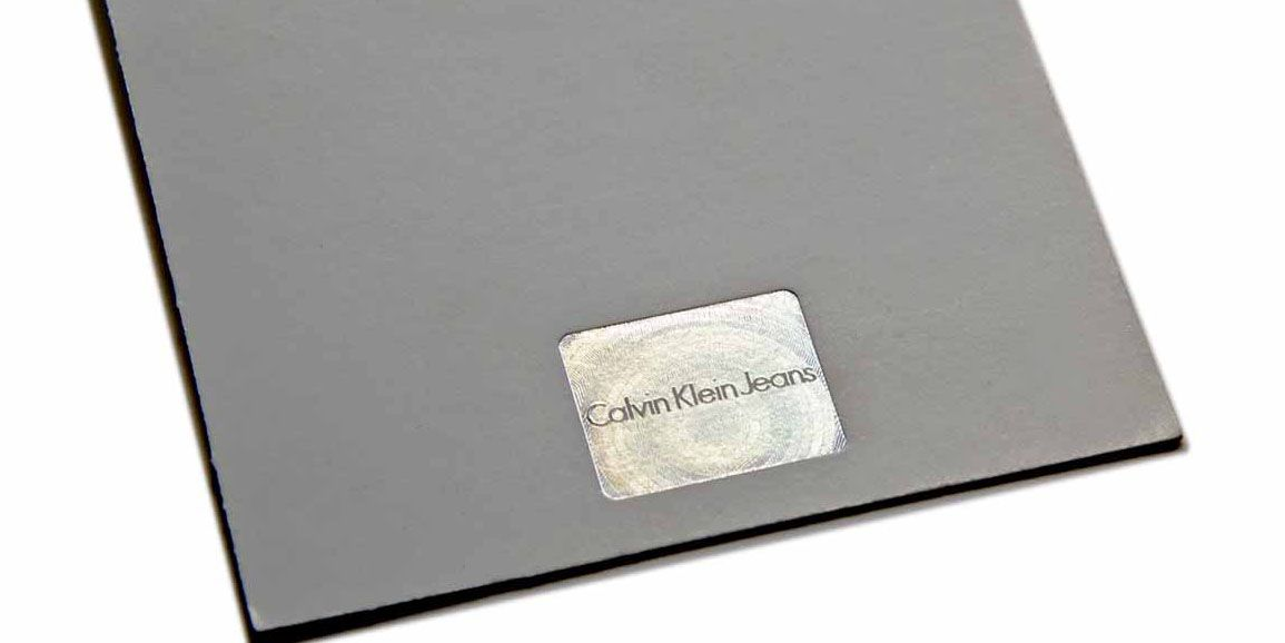 Calvin Klein stamp, foiled with a special MicroSecurFoil / anti-counterfeiting holographic microtextured die - design and dies manufacturing by gasperini.it