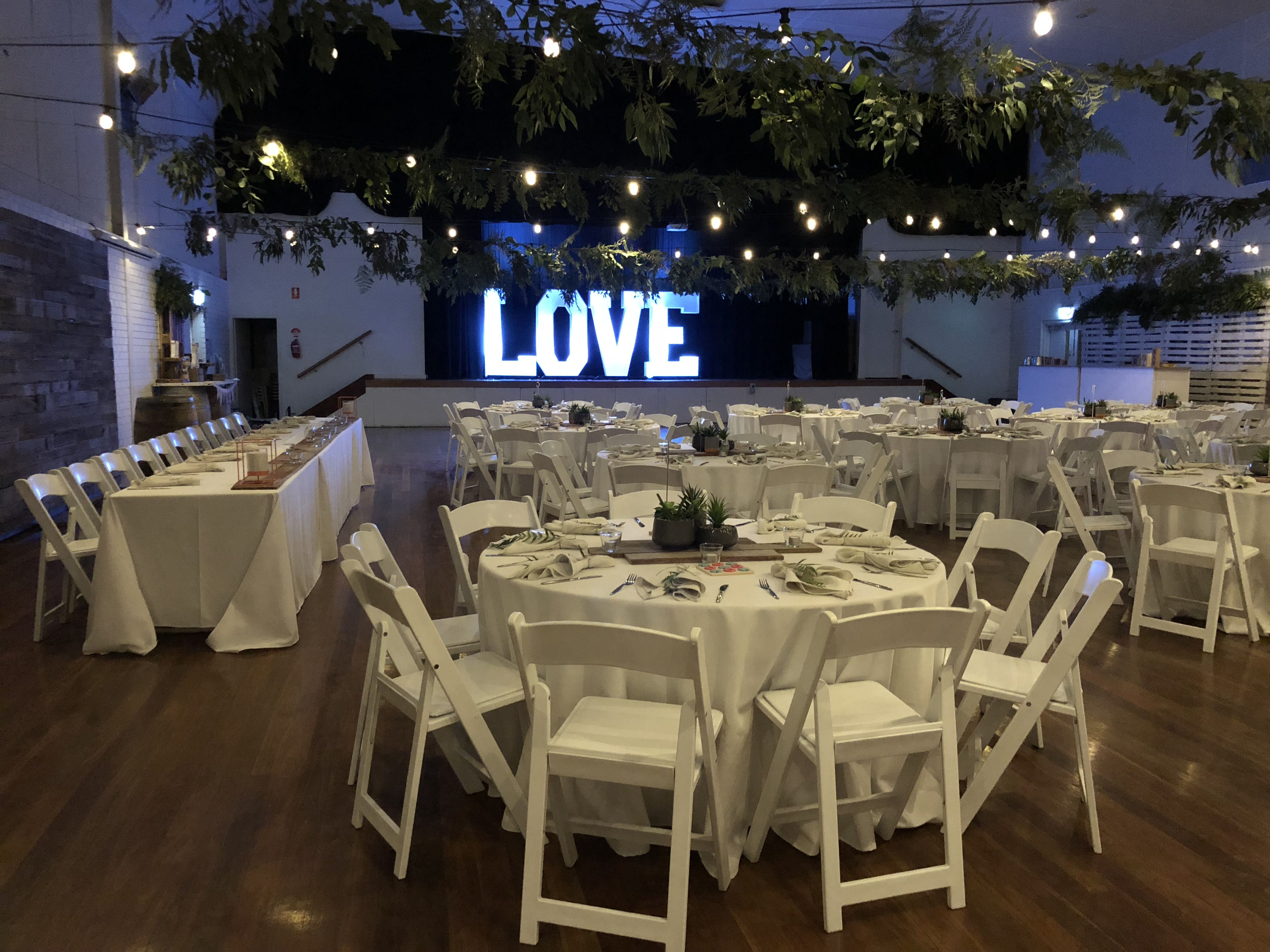 Rustic wedding hall transformation festoon lighting with foliage rustic timber bridal table back drop round tables with white gladiator chairs hire and