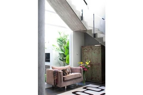 El acento en los detalles  En el hall, sillón rosado ($3.900 más género, Fradusco) y alfombra ($1.672, Vanina Mizrahi para Karavell). Florero de vidrio ($120, Chill Out Flores). En el hueco de la escalera se ubicó un ropero envejecido.